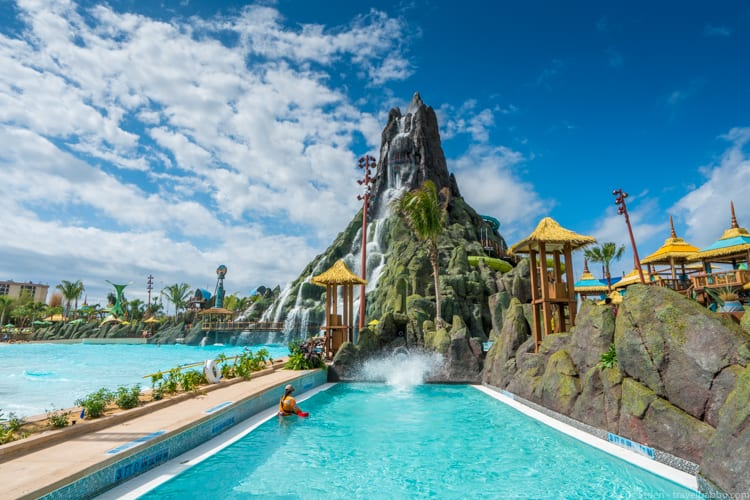 Volcano Bay: A person enters the splash pool from the Ko'okiri Body Plunge. You can see the transparent slide towards the top of the volcano.