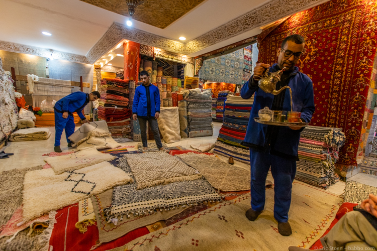 Morocco with Kids - Rug unrolling with tea